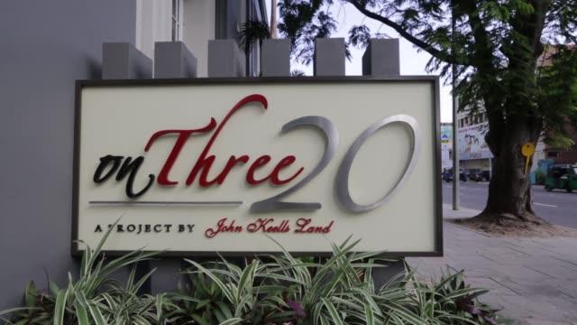 car drives past signage for the onthree20 condominium project developed by john keells land, a unit of john keells holdings plc, in colombo, sri... - tjänstekvinna bildbanksvideor och videomaterial från bakom kulisserna