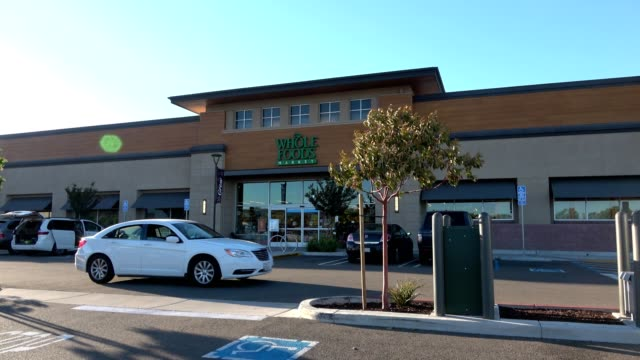 a car drives past the facade of the whole foods market grocery store in dublin california on a sunny day 2018 - whole foods market stock videos and b-roll footage