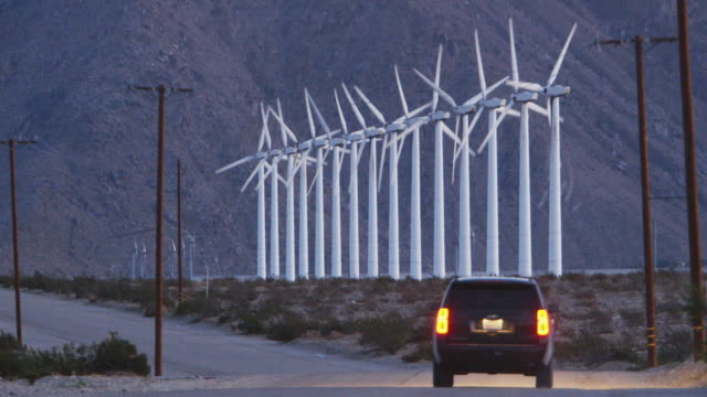 vídeos y material grabado en eventos de stock de ls a car drives past wind turbines in the desert / palm springs, california - luz trasera