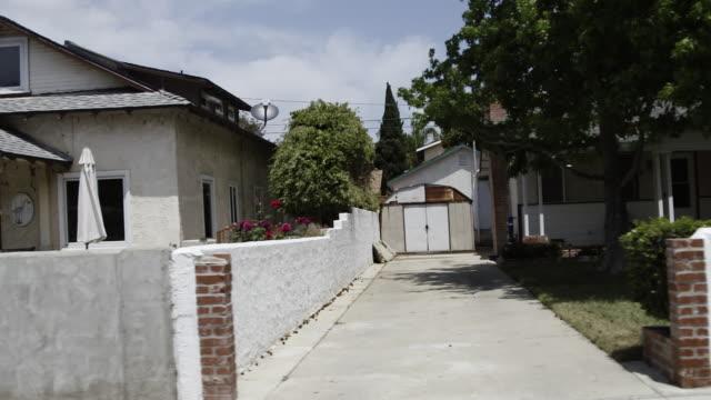 Car drives slowly along residential street POV from car