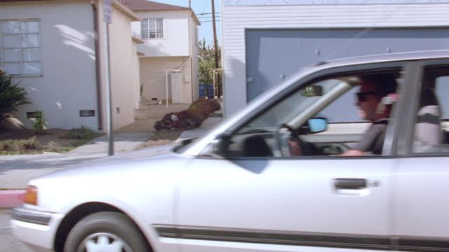 a car drives through a los angeles neighborhood. - stoppen stock-videos und b-roll-filmmaterial