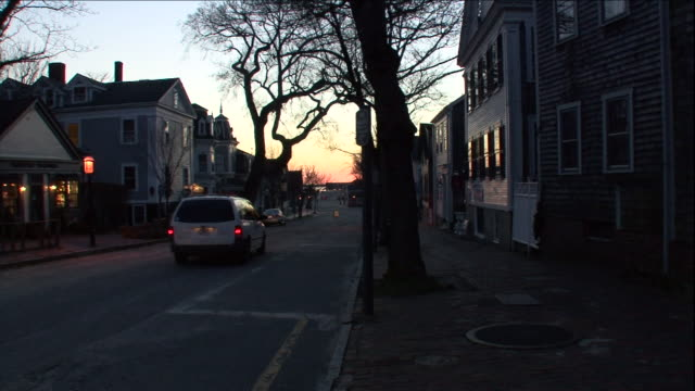 a car drives through a quiet neighborhood in the early morning. - massachusetts stock-videos und b-roll-filmmaterial
