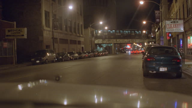 a car drives through an intersection towards an elevated train platform. - chicago illinois stock videos & royalty-free footage
