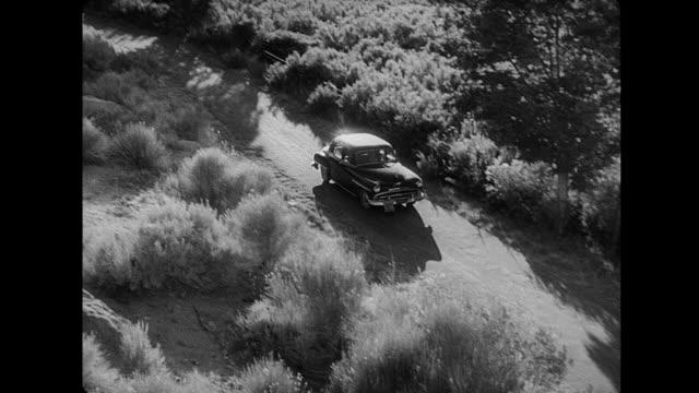 1953 a car drives through the desert - film noir style stock videos & royalty-free footage
