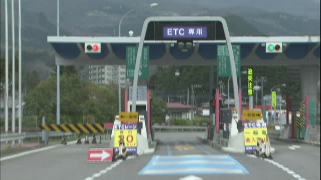 stockvideo's en b-roll-footage met a car drives through the etc toll-collection gate at the nikko exit of the nikko-utsunomiya road in tochigi prefecture, japan. - medium filmcompositietype