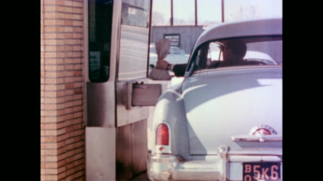 vidéos et rushes de car drives up to bank window / driver deposits bag of money / aerial of shopping mall and parking lot / mid century cars driving around the crowded... - société de consommation