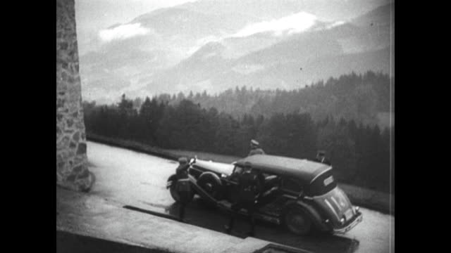 car drives up to berchtesgaden estate in bavaria germany / neville chamberlain and adolf hitler walk up steps to discuss peace options - adolf hitler stock-videos und b-roll-filmmaterial