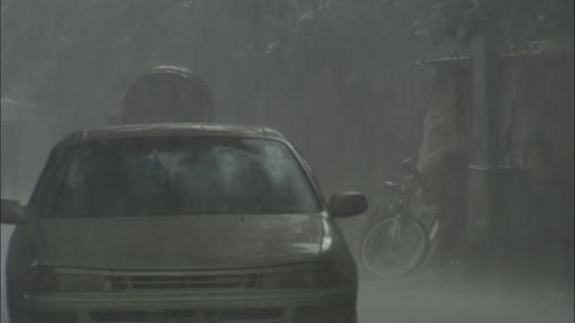 A car drives with its windscreen wipers working in a monsoon. Available in HD.