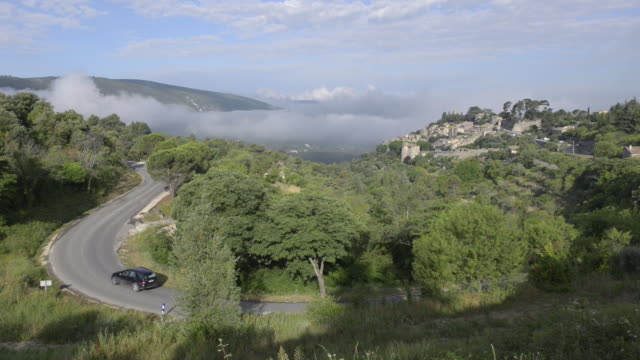 a car driving a mountain road at bonnieux village - luberon stock-videos und b-roll-filmmaterial