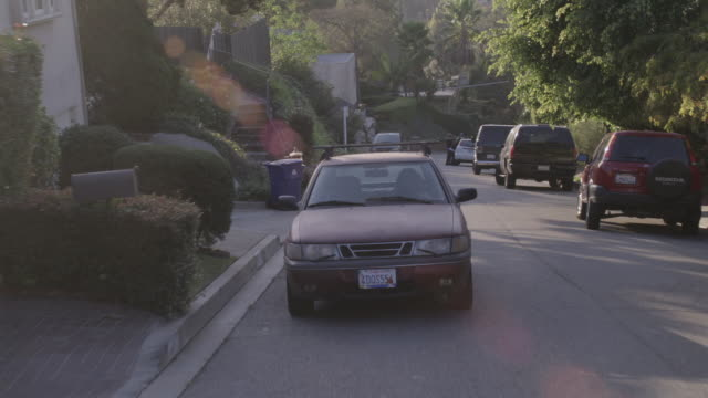 vidéos et rushes de rpov car driving along a narrow, hilly, residential street past parked cars and pedestrians pushing a stroller before pulling into a driveway - étroit