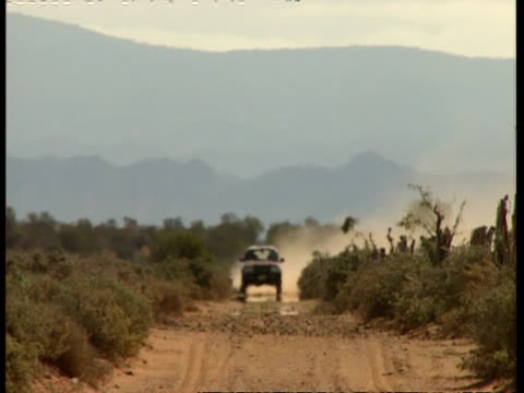 mwa car driving along dirt road in desert, heat haze, to camera - heat haze stock videos & royalty-free footage