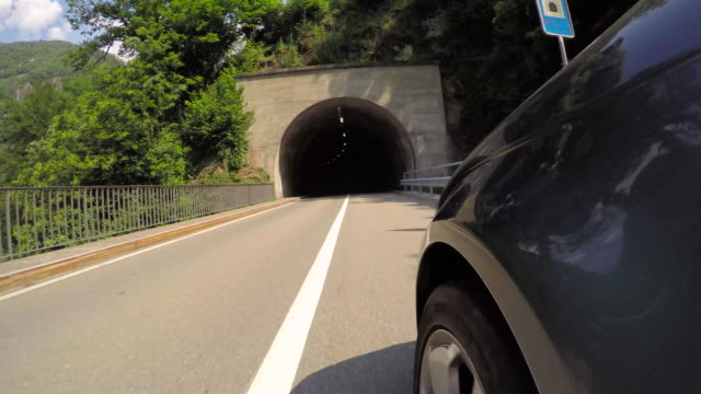 pov of car driving along paved road, through tunnels - tunnel stock videos & royalty-free footage