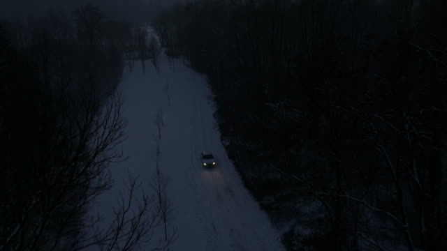 AERIAL Car driving along snow capped country road at night