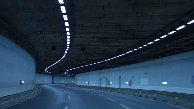 pov car driving at night in a tunnel on the highway - loopable moving image stock videos & royalty-free footage