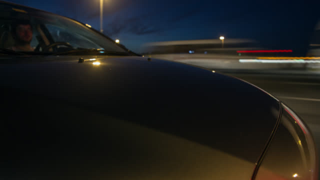 car driving at night on a dubai road with the hood in foreground. streaking reflections on the car's surface and streaking city background. - windschutzscheibe stock-videos und b-roll-filmmaterial