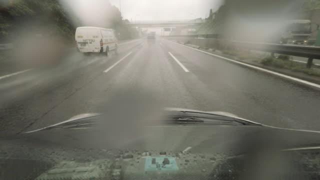 vídeos de stock, filmes e b-roll de carro dirigindo na estrada-chuvas 4 k - para brisa