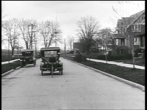 b/w 1919 car driving behind bike rider + hitting him / men rush to pick him up / newsreel - 1910 1919 stock videos & royalty-free footage