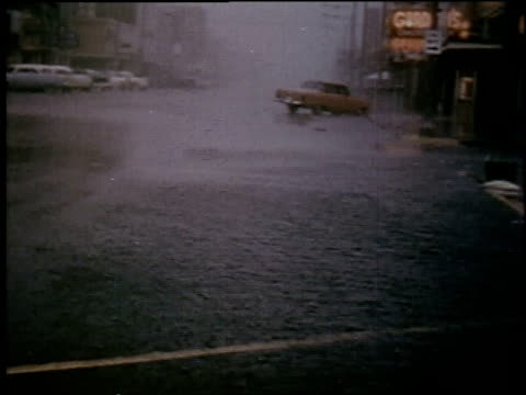 vidéos et rushes de car driving by in the rain / rain and wind blowing on street - 1957