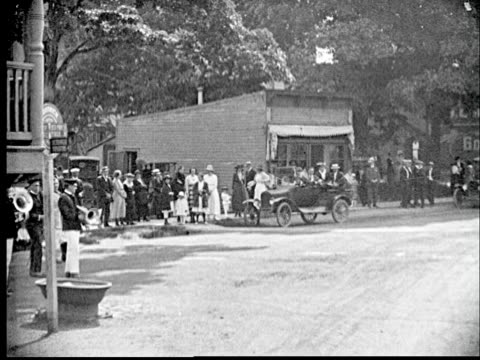 1920 B/W POV Car driving down dirt road / Boy riding on bicycle with American flag following / Street lined with cars from early 20th century / Cornwall, New York, USA