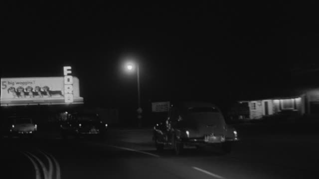 vidéos et rushes de 1956 pov car driving down road at night past motels and billboards on windy road / studio city, california - 1956