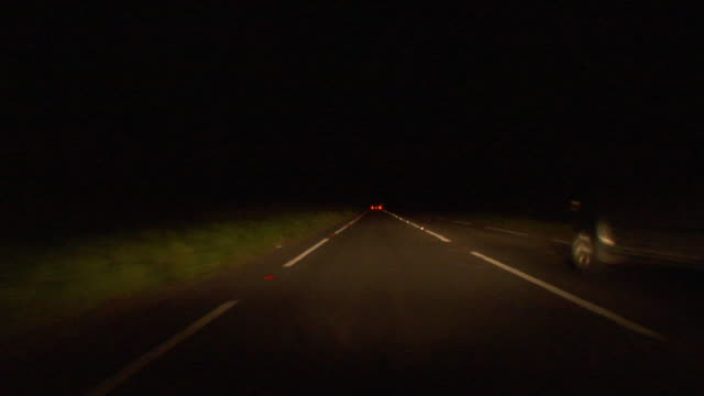 WS Car POV driving down road at night through Epping Forest and being passed by other cars/ London, England
