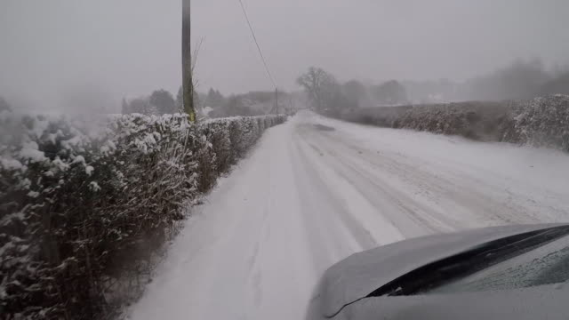 car driving down snow covered country road in hampshire - privatfahrzeug stock-videos und b-roll-filmmaterial