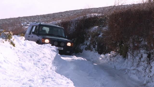 car driving down snowy road, dartmoor, uk - dartmoor stock videos & royalty-free footage
