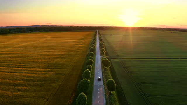 aerial car driving down the road in the countryside at sunset - back lit stock videos & royalty-free footage