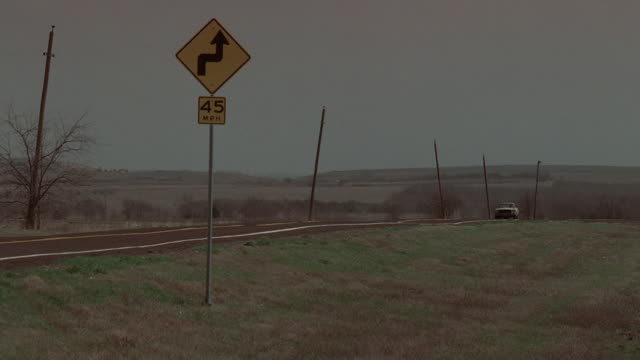 ws car driving down two-lane road, past speed limit sign / kaufman, texas, united states - breitwandformat stock-videos und b-roll-filmmaterial