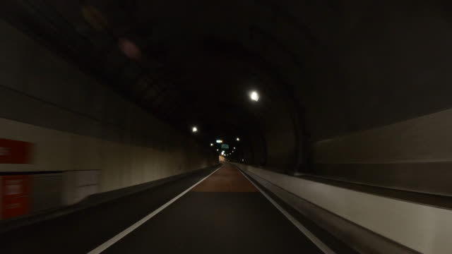 pov car driving in highway tunnel - headlight stock videos & royalty-free footage