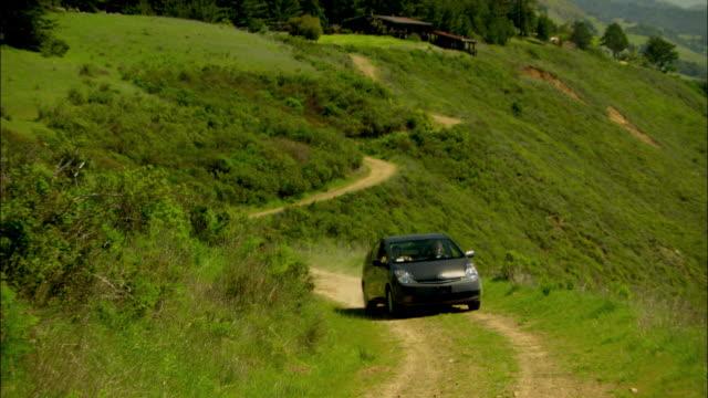 stockvideo's en b-roll-footage met ws, pan, car driving in mountain landscape along ocean coastline, big sur, california, usa - hybride voertuig
