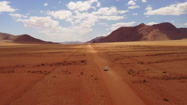 遠く離れた砂漠で運転するws車、ナミビア、アフリカ - ワイドショット点の映像素材/bロール