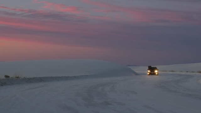 car driving in sand dune at sunset - ニューメキシコ州点の映像素材/bロール