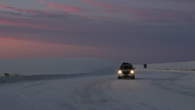 car driving in sand dune at sunset - 風致地区点の映像素材/bロール