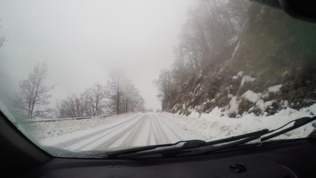 POV car driving in snow: mountain pass