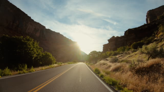 pov car driving in usa southwest: straight road and majestic sunset outdoors - journey stock videos & royalty-free footage