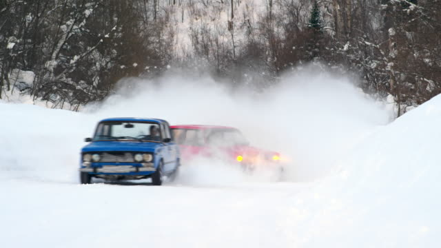 Car driving into snowdrift during race on snow in winter forest