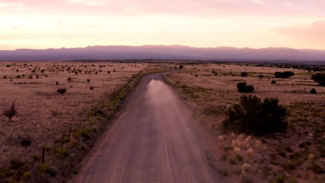 stockvideo's en b-roll-footage met auto rijden in de woestijn zonsondergang: new mexico - western usa