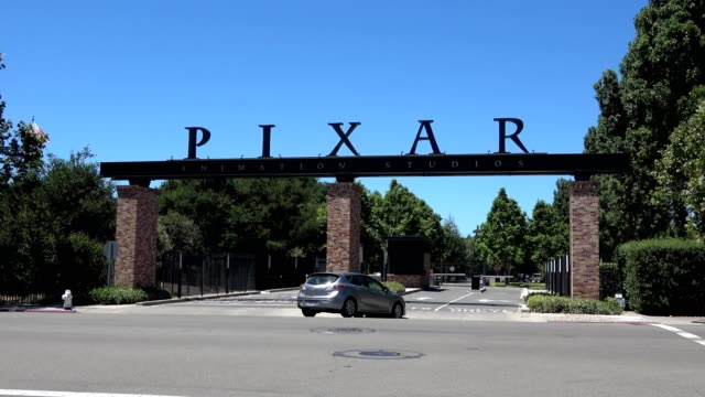 car driving into the entrance gate at headquarters of animation company pixar in downtown emeryville, california, june 12, 2018. - emeryville stock videos & royalty-free footage