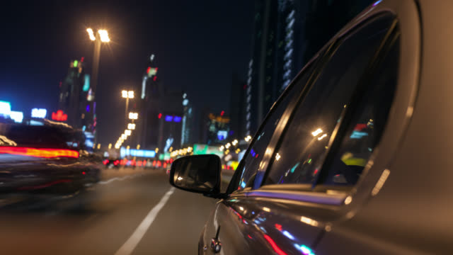 car driving night along dubai's sheikh zayed road through the downtown district with the side of the car in foreground. reflections in the car's surface and streaking city background. - wing mirror stock videos and b-roll footage