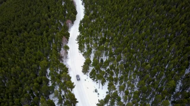 Car driving on a snowy road, viewed by drone