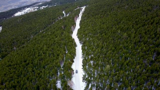 vídeos de stock e filmes b-roll de car driving on a snowy road, viewed by drone - perigo