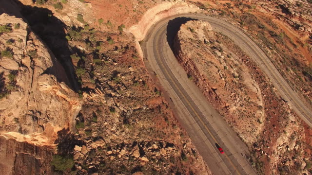 AERIAL Car driving on a winding road in desert