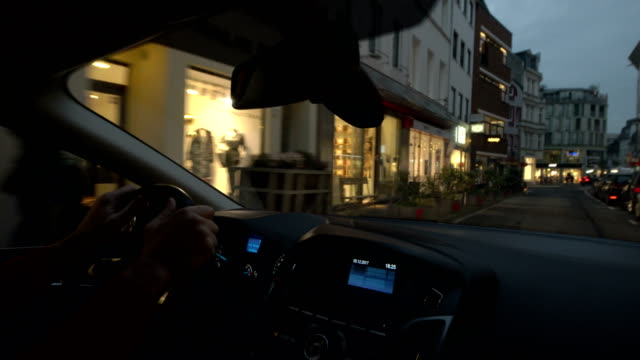 pov car driving on city street at dusk - steering wheel stock videos & royalty-free footage