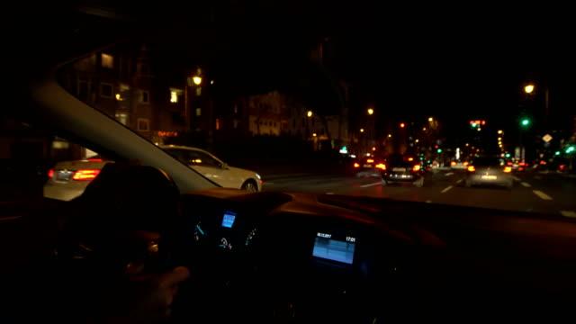 pov car driving on city street at night - car interior stock videos & royalty-free footage