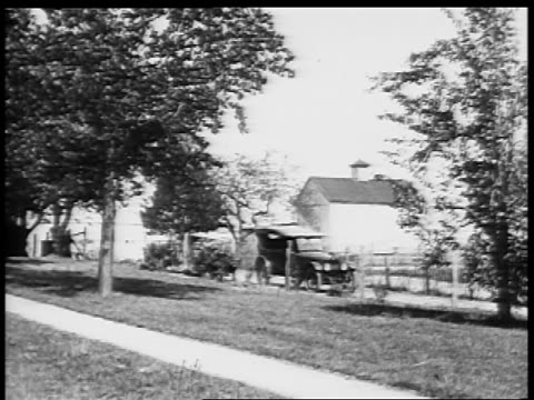B/W 1927 car driving on country road / educational