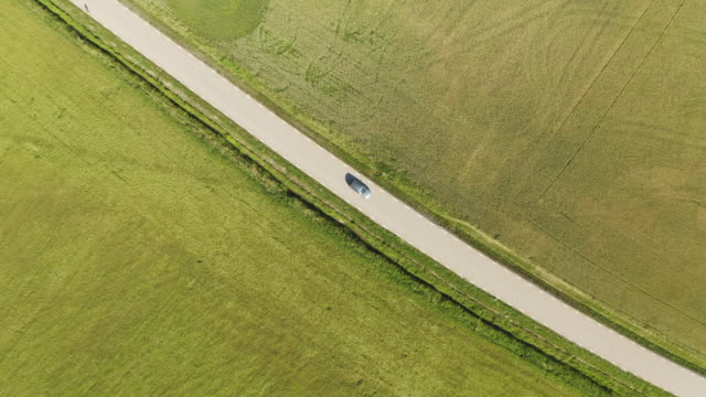 car driving on country road through wheat fields - sweden stock videos & royalty-free footage