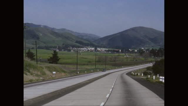 ws pov car driving on country road withsmall town and hills in background / united states - on the move video stock e b–roll