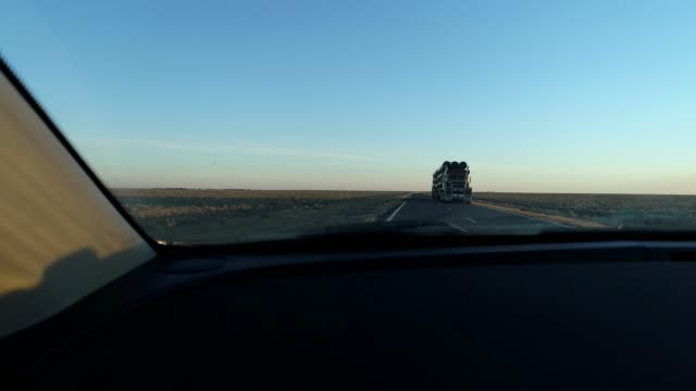 stockvideo's en b-roll-footage met car pov driving on desert highway at sunset - tweebaansweg