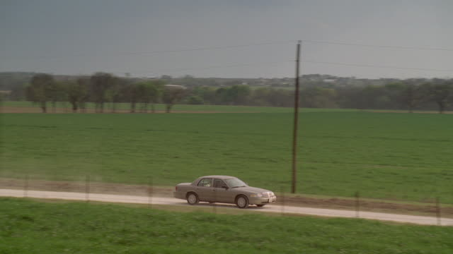 TS Car driving on dirt road and arriving at highway / United States